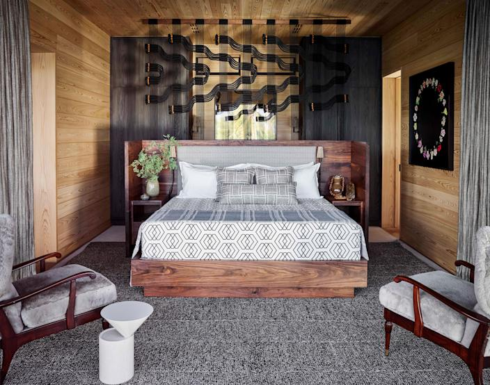 """<em>Lava Flow</em>, a 2019 """"circuit board"""" by Windy Chien that depicts the slow prowl of molten lava, divides the open format of the primary bedroom. A bathroom and dressing area in the back is ocean-facing, while the sleeping area looks toward the sacred mountain Mauna Kea for the sunrise. Vintage wingback armchairs by Paolo Buffa are covered in sheepskin—an unusual choice for island life, but de la Cruz insists that unlike leather, it's cool to the touch."""