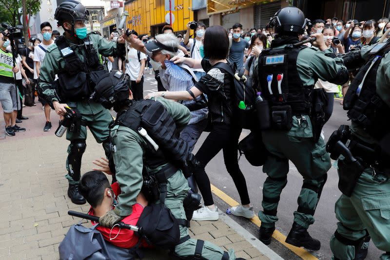 FILE PHOTO: Anti-government demonstrators scuffle with riot police during a lunch time protest as a second reading of a controversial national anthem law takes place in Hong Kong