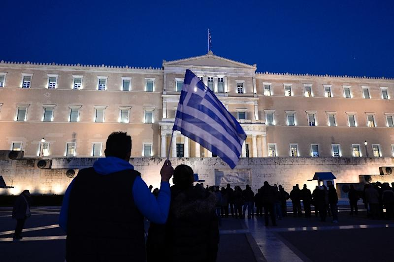 A man holds a Greek flag in front of the parliament in Athens as people gather in support to their government on February 20, 2015 (AFP Photo/Louisa Gouliamaki)