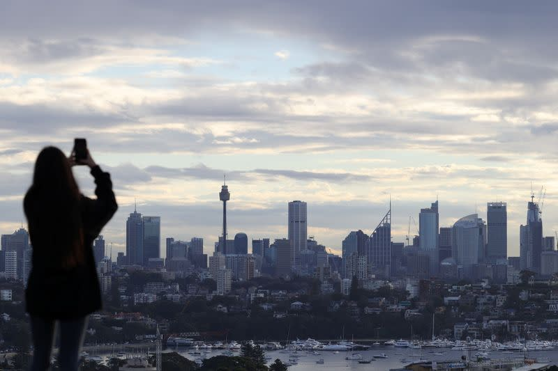 A woman stands on a hill overlooking the city centre skyline in Sydney