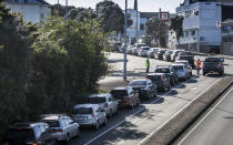 Cars queue at a COVID-19 test centre in Auckland, New Zealand, Thursday, Aug. 13, 2020. Health authorities in New Zealand are scrambling to trace the source of a new outbreak of the coronavirus as the nation's largest city goes back into lockdown. (AP Photo/Greg Bowker)