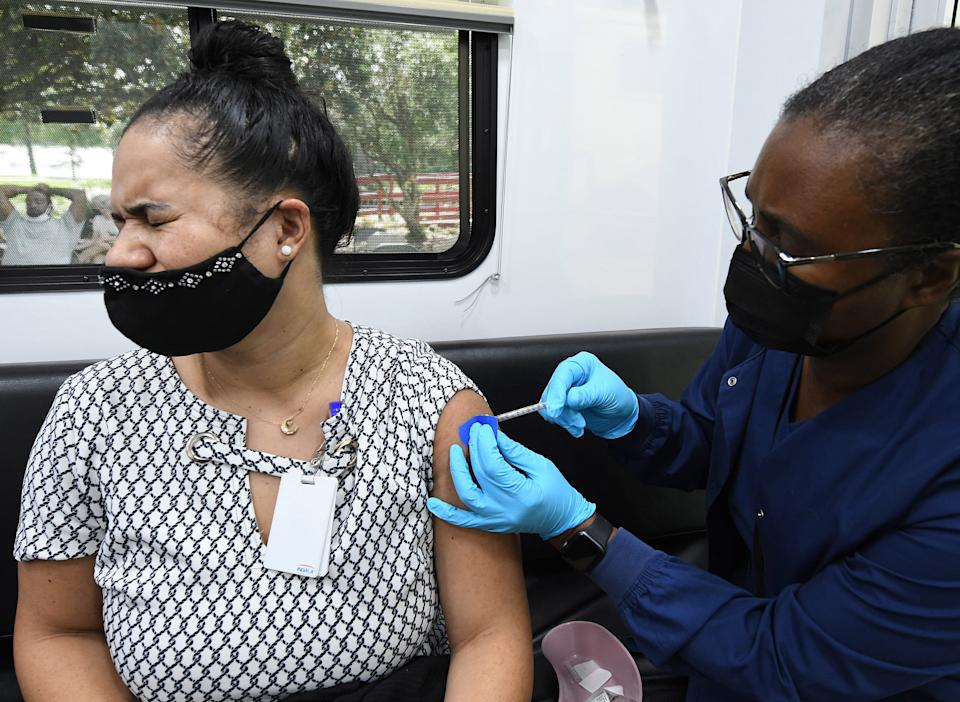 A health care worker, wearing a face mask and gloves, gives a shot to a woman at a mobile vaccination site