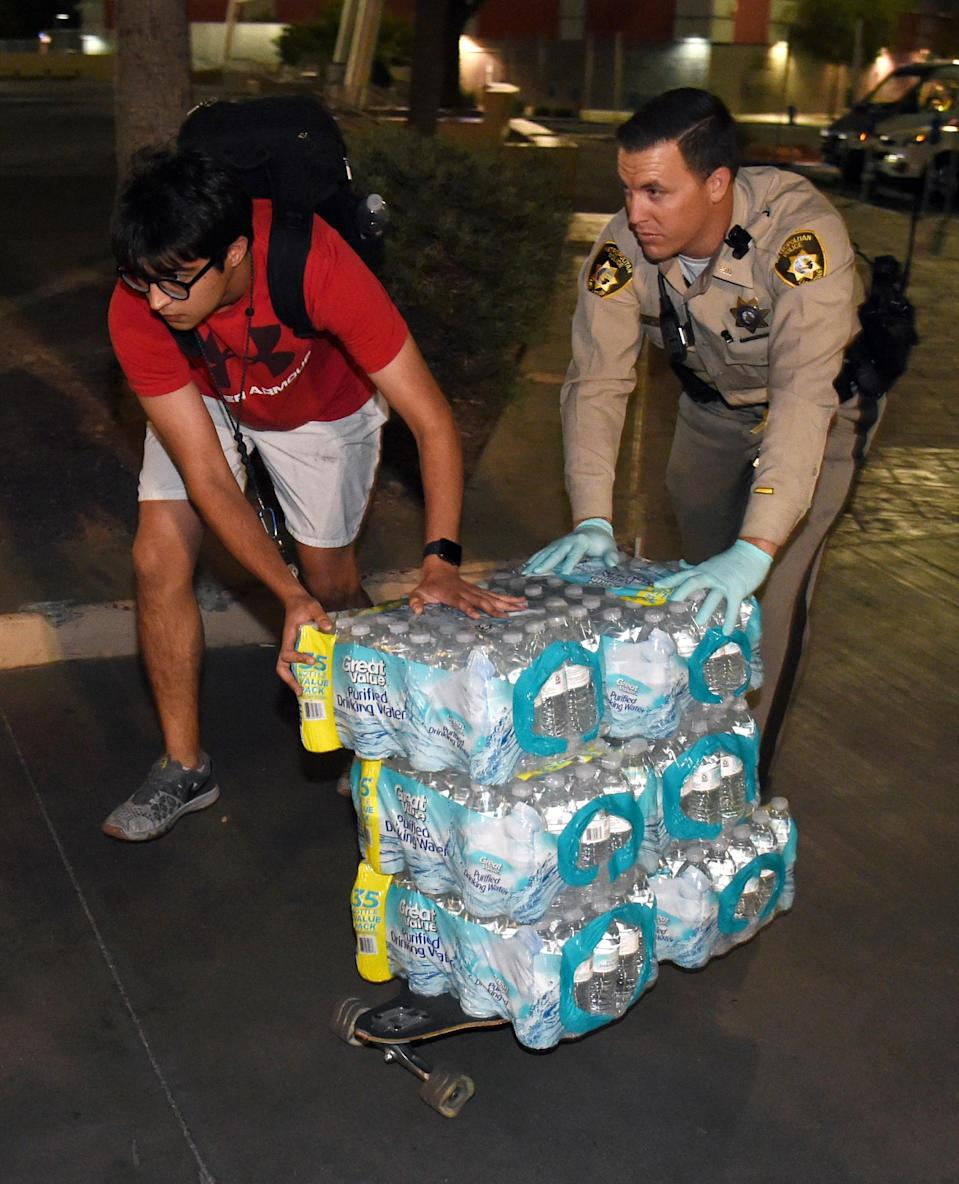 <p>UNLV student Ajay Narang (L) and a Las Vegas Metropolitan Police Department officer use Narang's skateboard to help deliver bottled water to people at the Thomas & Mack Center. (Getty) </p>
