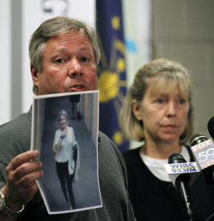 FILE - In this June 15, 2011 file photo, Robert and Charlene Spierer display a photo of their missing daughter Lauren Spierer taken by a video surveillance camera in her apartment building on the night she disappeared, during a news conference in Bloomington, Ind. A jury trial in a federal lawsuit against two men who were with a 20-year-old Indiana University student before she vanished in 2011 has been scheduled for next spring. Her parents claim in their lawsuit that Jason Rosenbaum and Corey Rossman gave her alcohol and didn't make sure she returned safely to her apartment, leading to her presumed death. (AP Photo/Michael Conroy, File)