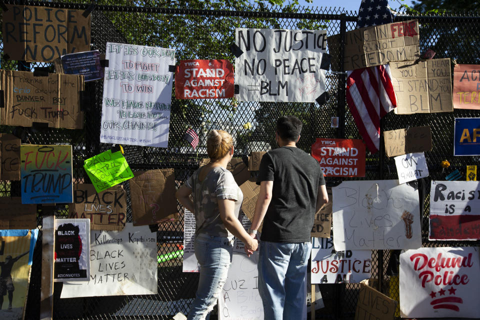 A couple reads signs left on a fence at Lafayette Square near the White House, during ongoing protests against police brutality and racism, on June 7, 2020 in Washington, DC. (Jose Luis Magana/AFP via Getty Images)