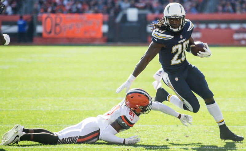 Oct 14, 2018; Cleveland, OH, USA; Los Angeles Chargers running back Melvin Gordon (28) eludes the tackle of Cleveland Browns cornerback Denzel Ward (21) during the second half at FirstEnergy Stadium. Mandatory Credit: Ken Blaze-USA TODAY Sports
