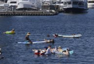 Groups of people float on inflatable devices on Lake Union during a heat wave hitting the Pacific Northwest, Sunday, June 27, 2021, in Seattle. A day earlier, a record high was set for that date with more record highs expected today and Monday. (AP Photo/John Froschauer)