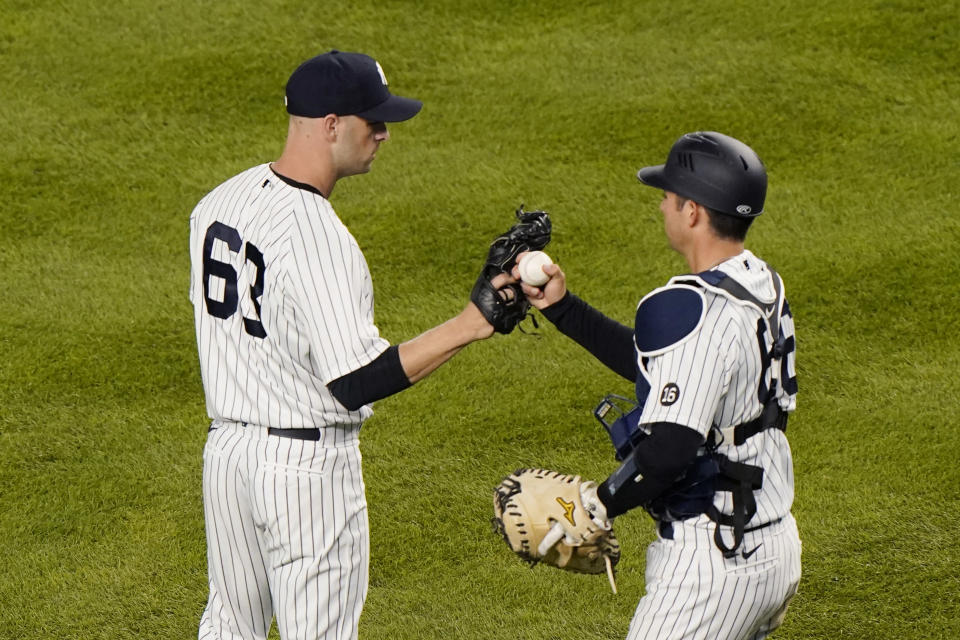 New York Yankees catcher Kyle Higashioka (66) congratulates Yankees relief pitcher Lucas Luetge (63) after the Yankees 7-2 victory over the Baltimore Orioles in a baseball game, Tuesday, April 6, 2021, at Yankee Stadium in New York. Luetge allowed a two-run, home run to Baltimore Orioles Rio Ruiz. (AP Photo/Kathy Willens)
