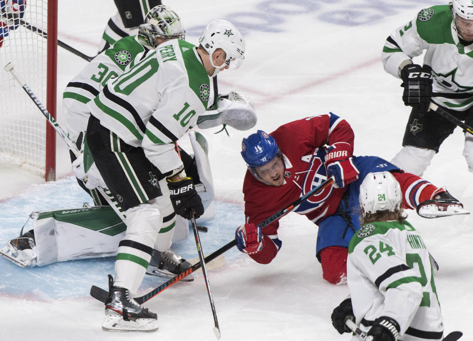 Montreal Canadiens' Brendan Gallagher (11) loses his footing as he moves in on Dallas Stars goaltender Ben Bishop as Stars' Corey Perry (10) and Roope Hintz (24) defend during the first period of an NHL hockey game Saturday, Feb. 15, 2020, in Montreal. (Graham Hughes/The Canadian Press via AP)
