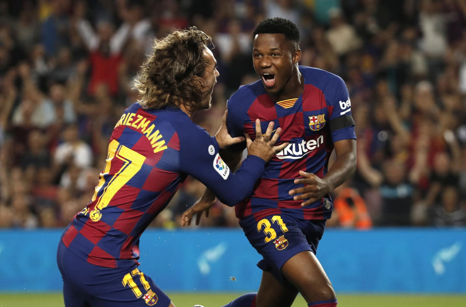 Barcelona's Ansu Fati, right, celebrates with teammate Barcelona's Antoine Griezmann after scoring the opening goal during the Spanish La Liga soccer match between FC Barcelona and Valencia CF at the Camp Nou stadium in Barcelona, Spain, Saturday, Sep. 14, 2019. (AP Photo/Joan Monfort)