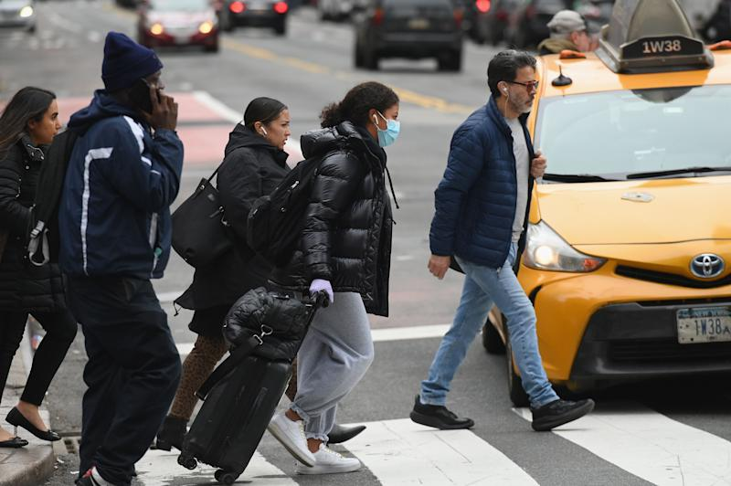 A woman wearing a face mask and gloves pulls her luggage as she walks through Manhattan on March 12, 2020 in New York City. - New York Governor Andrew Cuomo on March 12, 2020 banned public gatherings of more than 500 people, including shows in Manhattan's iconic Broadway theater district. Only schools, hospitals, nursing homes and mass transit facitilities are excepted from the rule -- which goes into effect for Broadway at 5:00 pm March 12, 2020, and 24 hours later everywhere else, Cuomo told journalists. (Photo by Angela Weiss / AFP) (Photo by ANGELA WEISS/AFP via Getty Images)
