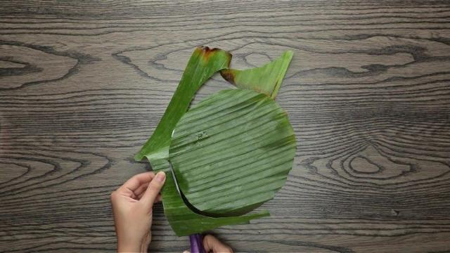 Cutting a circle out of banana leaf with scissors
