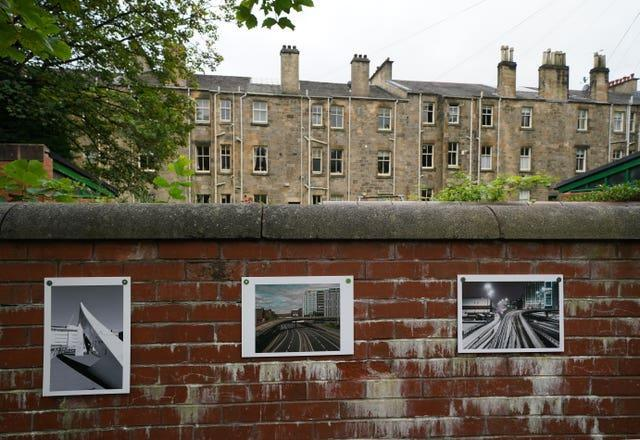 Photographs attached to a wall as part of the exhibition