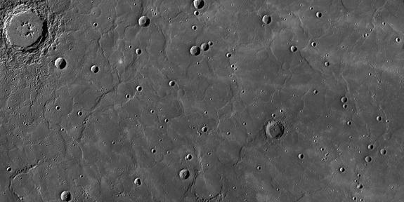 """This view from NASA's Messenger spacecraft orbiting Mercury shows a region of smooth, volcanic plains that have been heavily modified by tectonic structures termed """"wrinkle ridges,"""" low, sinuous features that form when lavas cool and subside, c"""
