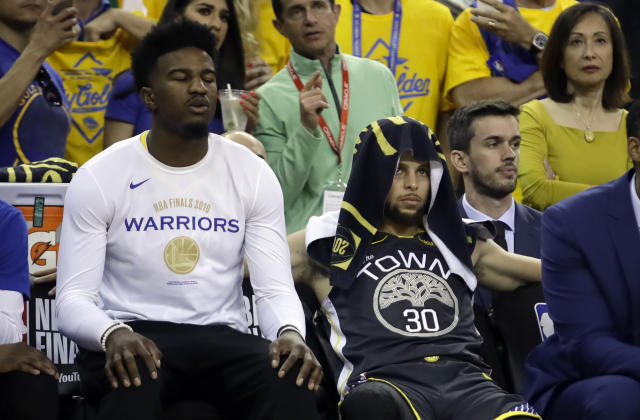 Golden State Warriors forward Jordan Bell, left, sits on the bench next to guard Stephen Curry (30) during the second half of Game 6 of basketball's NBA Finals against the Toronto Raptors in Oakland, Calif., Thursday, June 13, 2019. (AP Photo/Ben Margot)
