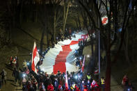 People carry a giant historical flag of Belarus during a celebration 103rd anniversary of the declaration of the Belarusian People's Respublic, in Vilnius, Lithuania, Thursday, March 25, 2021. Freedom Day is an unofficial holiday in Belarus celebrated on 25 March to commemorate the declaration of independence by the Belarusian Democratic Republic on that date in 1918.(AP Photo/Mindaugas Kulbis)