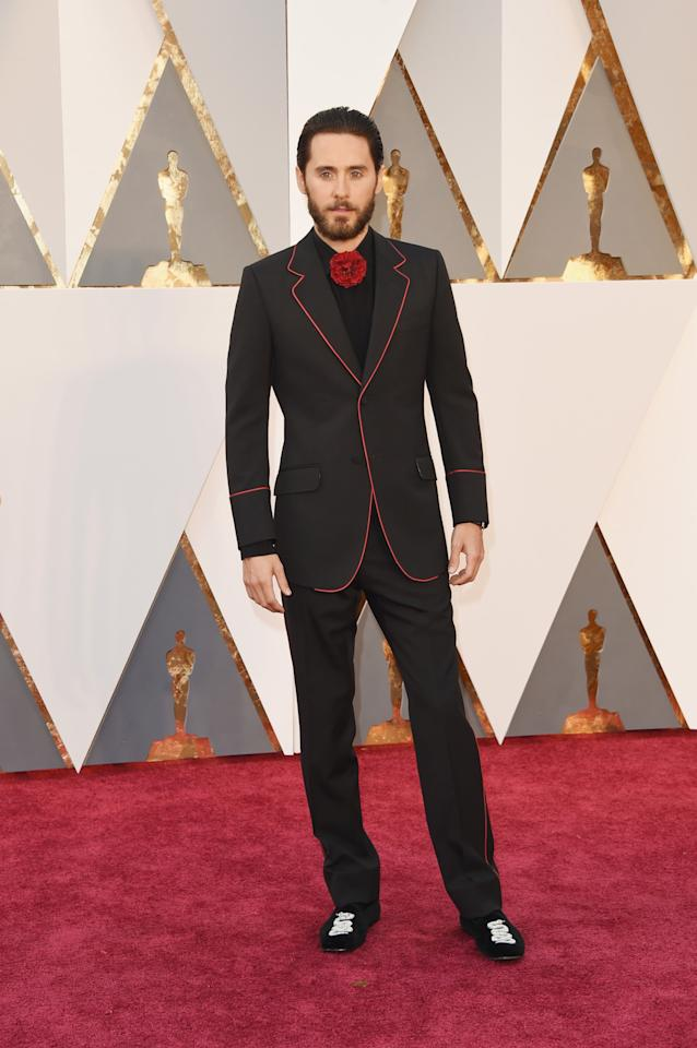 <p>Jared Leto brought Gucci designer Alessandro Michele as his date to the Oscars this year — and the duo brought surrealism to the red carpet. In an avant-garde tuxedo with red piping, serpentine velour slippers, and a festive floral tie, the actor looked characteristically stand-out.</p>