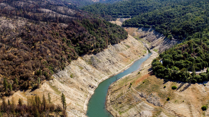 Dry banks rise above water in Lake Oroville on Sunday, May 23, 2021, in Oroville, Calif. At left are trees scorched in the 2020 North Complex Fire. At the time of this photo, the reservoir was at 39 percent of capacity and 46 percent of its historical average. California officials say the drought gripping the U.S. West is so severe it could cause one of the state's most important reservoirs to reach historic lows by late August, closing most boat ramps and shutting down a hydroelectric power plant during the peak demand of the hottest part of the summer. (AP Photo/Noah Berger)