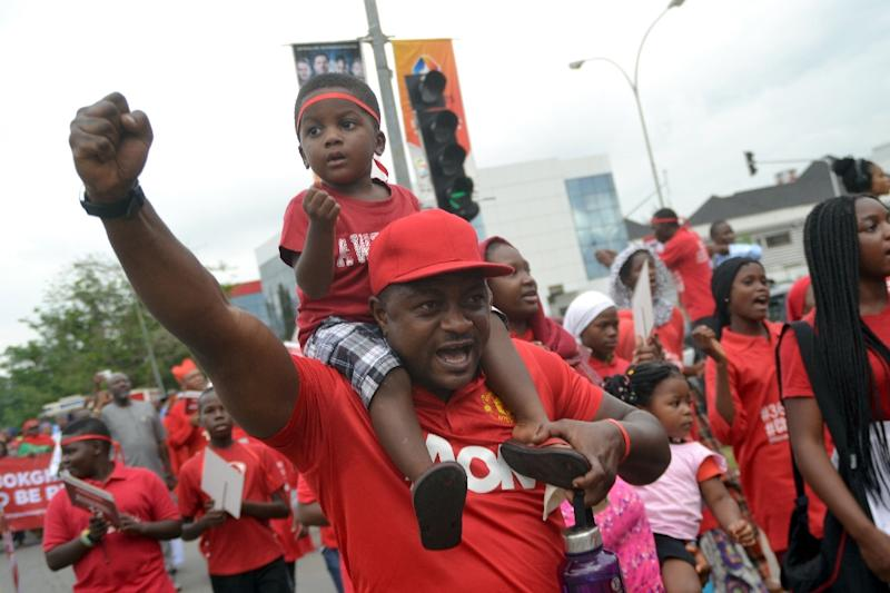 A man chants carrying his child on his shoulders during a rally to mark 500 days since the abductions of the Chibok schoolgirls by Boko Haram militants, in Abuja on August 27, 2015 (AFP Photo/)