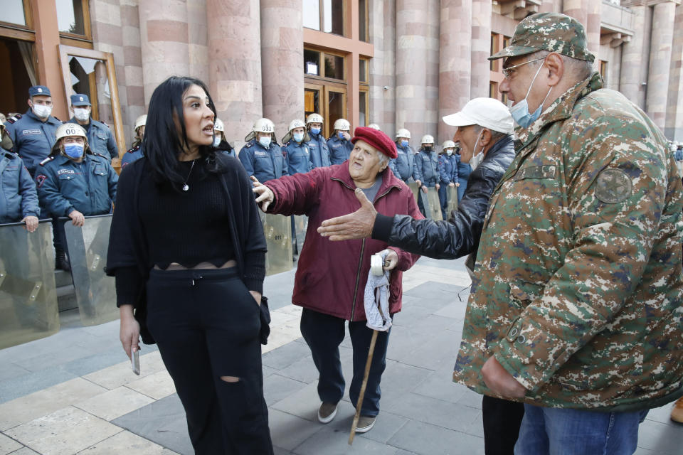 """People argue as the police officers guard in front of the government building in Yerevan, Armenia, Tuesday, Nov. 10, 2020. Thousands of people streamed to the main square in the Armenian capital early Tuesday to protest the agreement to halt fighting over the Nagorno-Karabakh region, many shouting """"We won't give up our land."""" Some of them broke into the main government building, saying they were searching for Pashinian, who apparently had already departed. (AP Photo/Dmitri Lovetsky)"""
