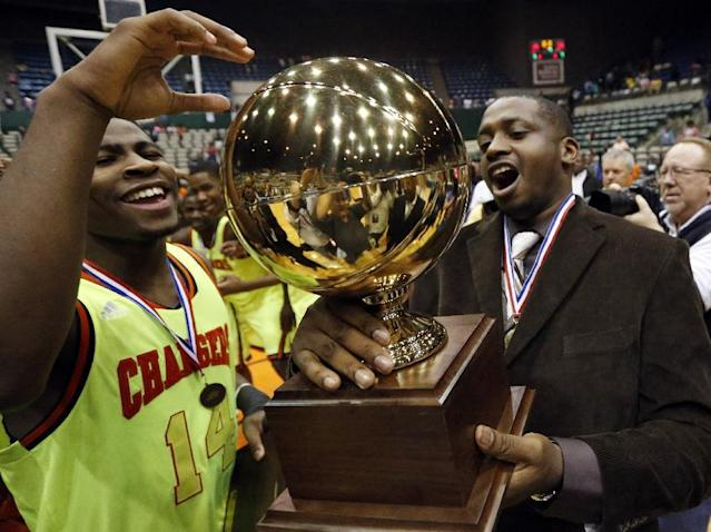 Callaway guard Malik Newman (14) and coach David Sanders hold the trophy as they celebrate Callaway's 49-33 win over Vicksburg in the MHSAA boys' Class 5A championship basketball game in Jackson, Miss., Friday, March 14, 2014. (AP Photo/Rogelio V. Solis)