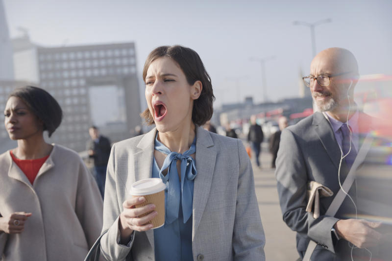 Tired businesswoman with coffee yawning on sunny morning urban pedestrian bridge