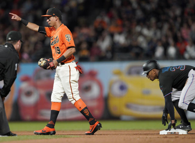 San Francisco Giants shortstop Mauricio Dubon (19) points back to catcher Buster Posey after getting the out on a steal attempt by Miami Marlins' Magneuris Sierra, right, during the seventh inning of a baseball game Friday, Sept. 13, 2019, in San Francisco. (AP Photo/Tony Avelar)