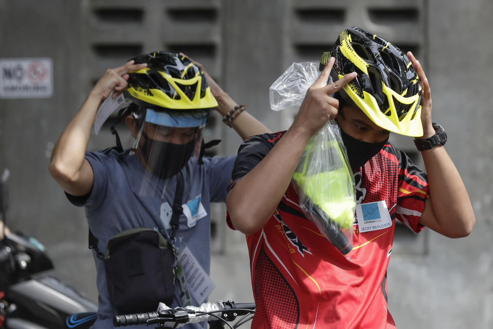 Recipients of bicycles from the Benjamin Canlas Courage to be Kind Foundation wear helmets before riding their new bicycles outside a building at the financial district of Manila, Philippines, Saturday, July 11, 2020. Restricted public transportation during the lockdown left many Filipinos walking for hours just to reach their jobs. The foundation saw the need and gave away mountain bikes to nominated individuals who are struggling to hold on to their jobs in a country hard hit by the coronavirus. (AP Photo/Aaron Favila)