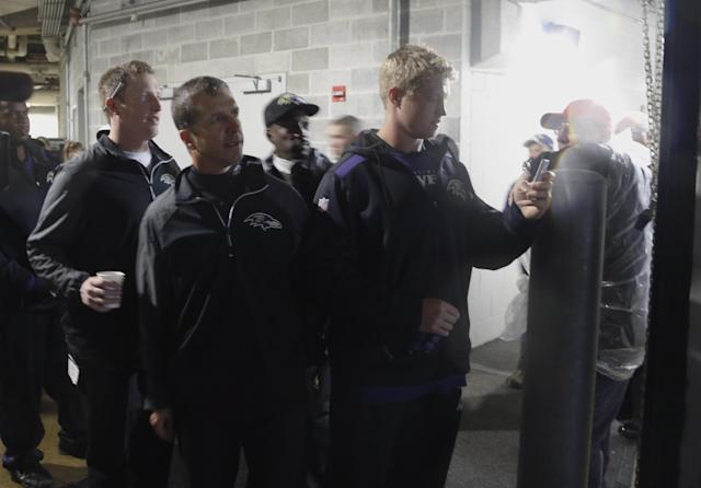 Baltimore Ravens head coach John Harbaugh, center, watches the severe storm passing through over Soldier Field from the tunnel during the first half of an NFL football game against the Chicago Bears, Sunday, Nov. 17, 2013, in Chicago. Play was suspended in the game. (AP Photo/Charles Rex Arbogast)