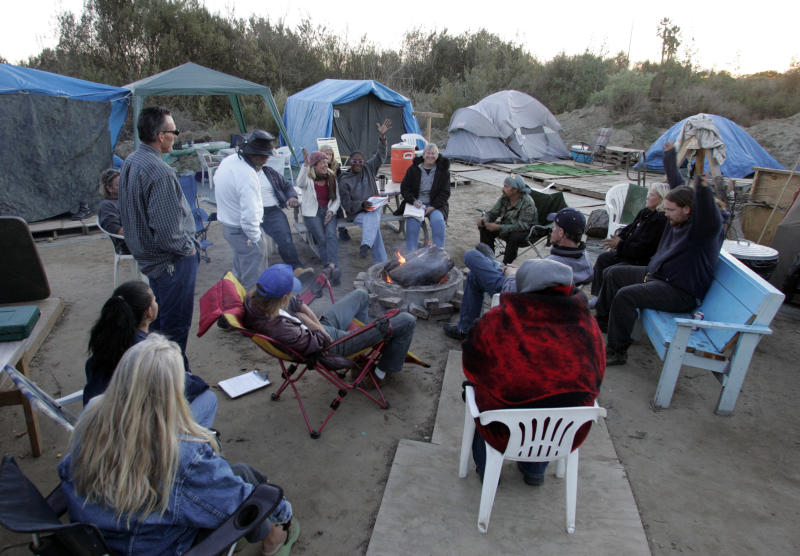 Camp residents vote on an issue. Homeless residents of River Haven, a tent encampment near the banks of the Santa Clara river, held a community which is headed by a camp council. The council meets weekly with all residents. The residents discussed several issues ranging from write–ups for breaking camp rules to ideas for a Secret Santa gift exchange. (Photo by Stephen Osman/Los Angeles Times via Getty Images)