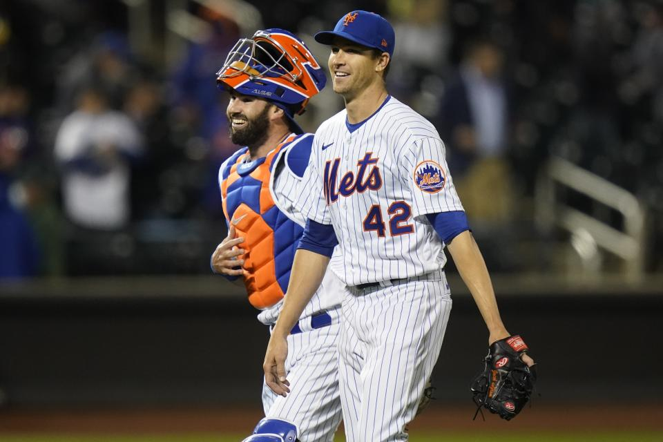 New York Mets starting pitcher Jacob deGrom, right, and catcher Tomas Nido, left, celebrate after a baseball game against the Washington Nationals Friday, April 23, 2021, in New York. The Mets won 6-0. (AP Photo/Frank Franklin II)
