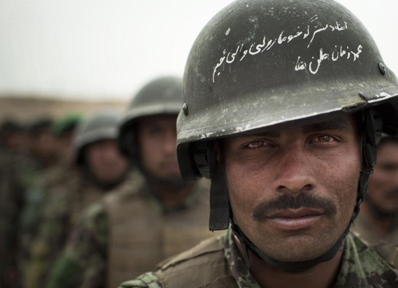 FILE- This May 16, 2012 file photo shows Afghan National Army soldier Mohammed Zaman lining up with other soldiers prior to a patrol in Logar province, eastern Afghanistan. A small love poem to his country is scratched on the surface of his helmet. Relations between Pakistan and Afghanistan have not been good in recent years, with Afghanistan often blaming Pakistan for supporting insurgents that are fighting both NATO troops and government forces. Major attacks and suicide bombings are regularly blamed on Pakistan, playing to a domestic audience that increasingly considers its neighbor responsible for the war.(AP Photo/Anja Niedringhaus, File)