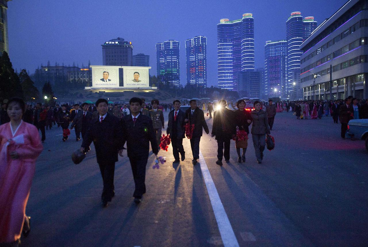 North Koreans walk past two mosaics of the late leaders Kim Il Sung and Kim Jong Il after a statue unveiling ceremony in Pyongyang, North Korea, Friday, April 13, 2012. (AP Photo/David Guttenfelder)