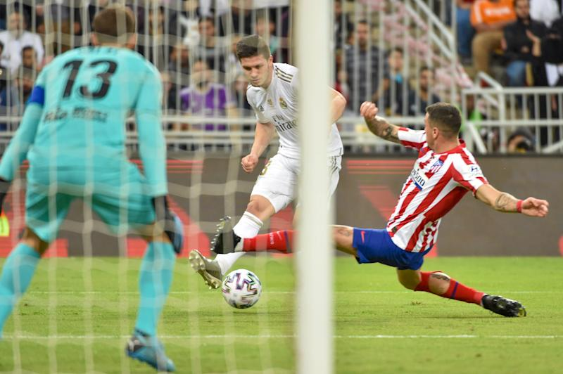 Real Madrid's Serbian forward Luka Jovic (C) is tackled by Atletico Madrid's Uruguayan defender Jose Gimenez (R) during the Spanish Super Cup final between Real Madrid and Atletico Madrid on January 12, 2020, at the King Abdullah Sports City in the Saudi Arabian port city of Jeddah. (Photo by FAYEZ NURELDINE / AFP) (Photo by FAYEZ NURELDINE/AFP via Getty Images)