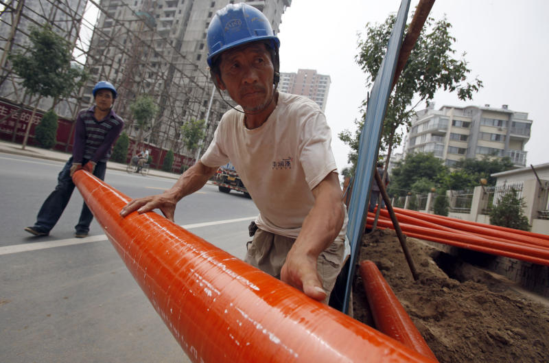 Workers move piping at a construction site in Beijing, China, Wednesday, July 13, 2011. China's rapid economic growth slowed in the latest quarter to a still robust 9.5 percent, easing fears of an abrupt slowdown and giving Beijing room to tighten controls to fight surging inflation.  (AP Photo)