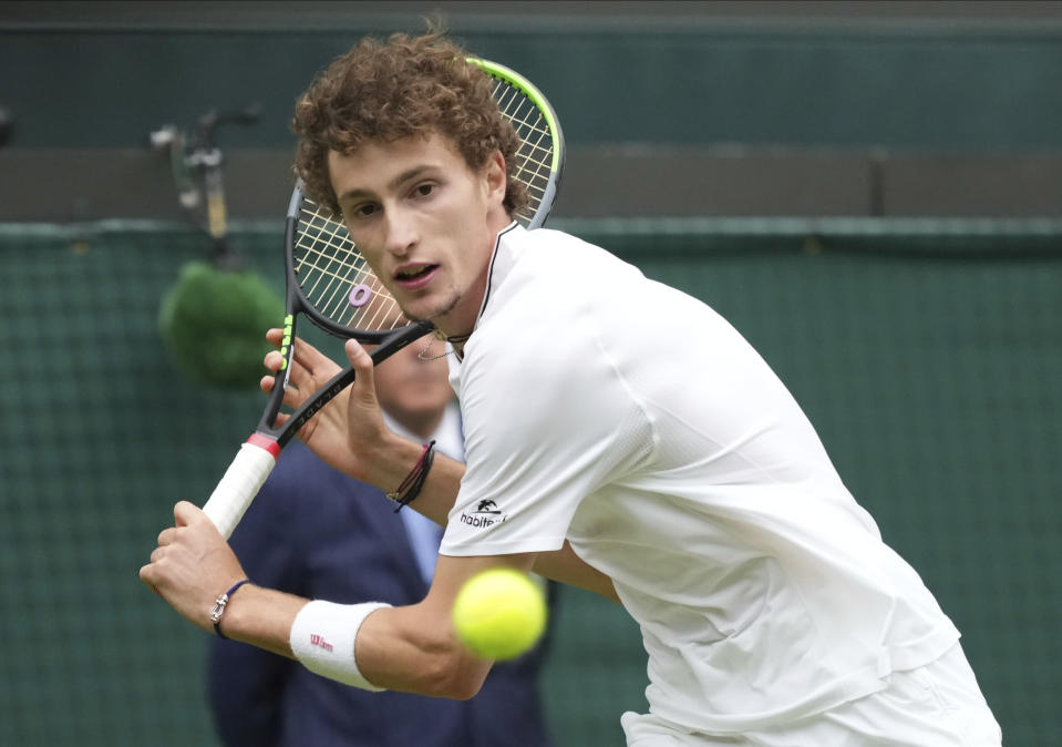 Ugo Humbert of France plays a return to Australia's Nick Kyrgios during the men's singles first round match on day three of the Wimbledon Tennis Championships in London, Wednesday June 30, 2021. (AP Photo/Alberto Pezzali)