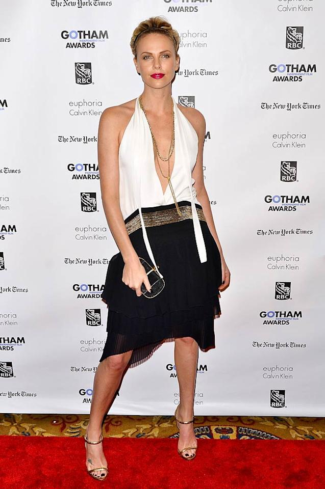 "No wonder Charlize Theron hasn't been single in 17 years! The star of the upcoming flick ""Young Adult"" rocked the red carpet at the Gotham Independent Film Awards in a black-and-white 1920s-inspired Gucci creation, and wisely swept back her hair in a headband, which allowed her to showcase her best accessory -- her gorgeous face. Charlize completed the sexy look with a gold necklace, gold sandals, and a hot Alexander McQueen clutch. (11/28/2011)"