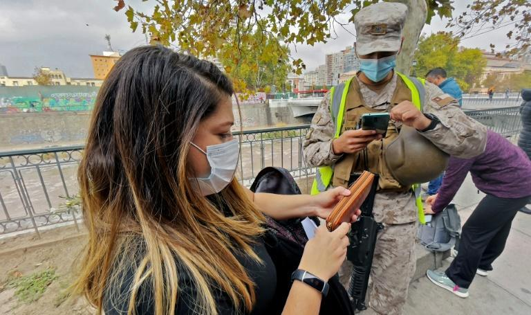 A soldier checks a pedestrian at a checkpoint in the Chilean capital Santiago as the country imposes a Covid-19 lockdown -- despite encouraging vaccination rates