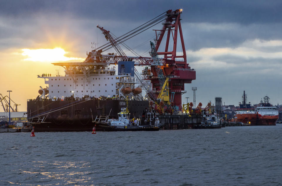 """Tugboats get into position on the Russian pipe-laying vessel """"Fortuna"""" in the port of Wismar, Germany, Thursday, Jan 14, 2021. The special vessel is being used for construction work on the German-Russian Nord Stream 2 gas pipeline in the Baltic Sea. ( Jens Buettner/dpa via AP)"""