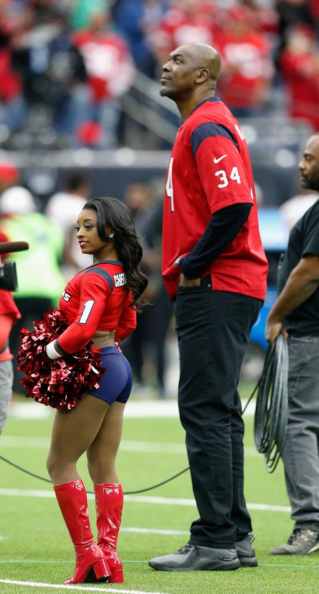 <p>Honorary cheerleader Simone Biles and Homefield Advantage Captain Hakeem Olajuwon during a game between the San Francisco 49ers v Houston Texans at NRG Stadium on December 10, 2017 in Houston, Texas. (Photo by Bob Levey/Getty Images) </p>