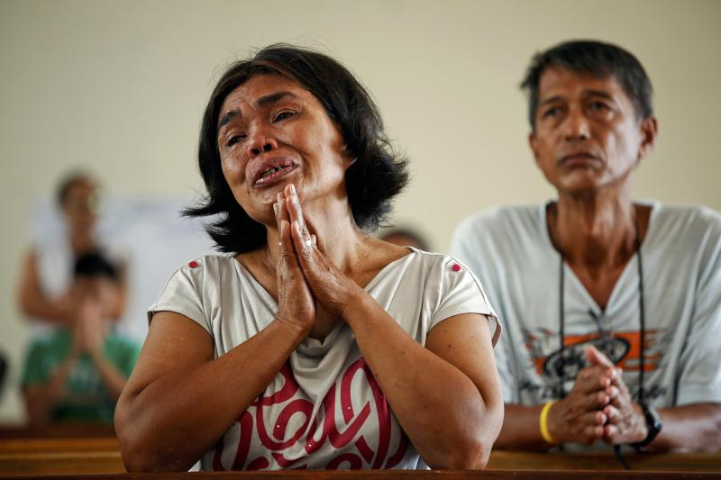 Capidos cries thanking God that she and her family survived typhoon Haiyan as she prays during Sunday Mass at the damaged Santo Nino Church in Tacloban