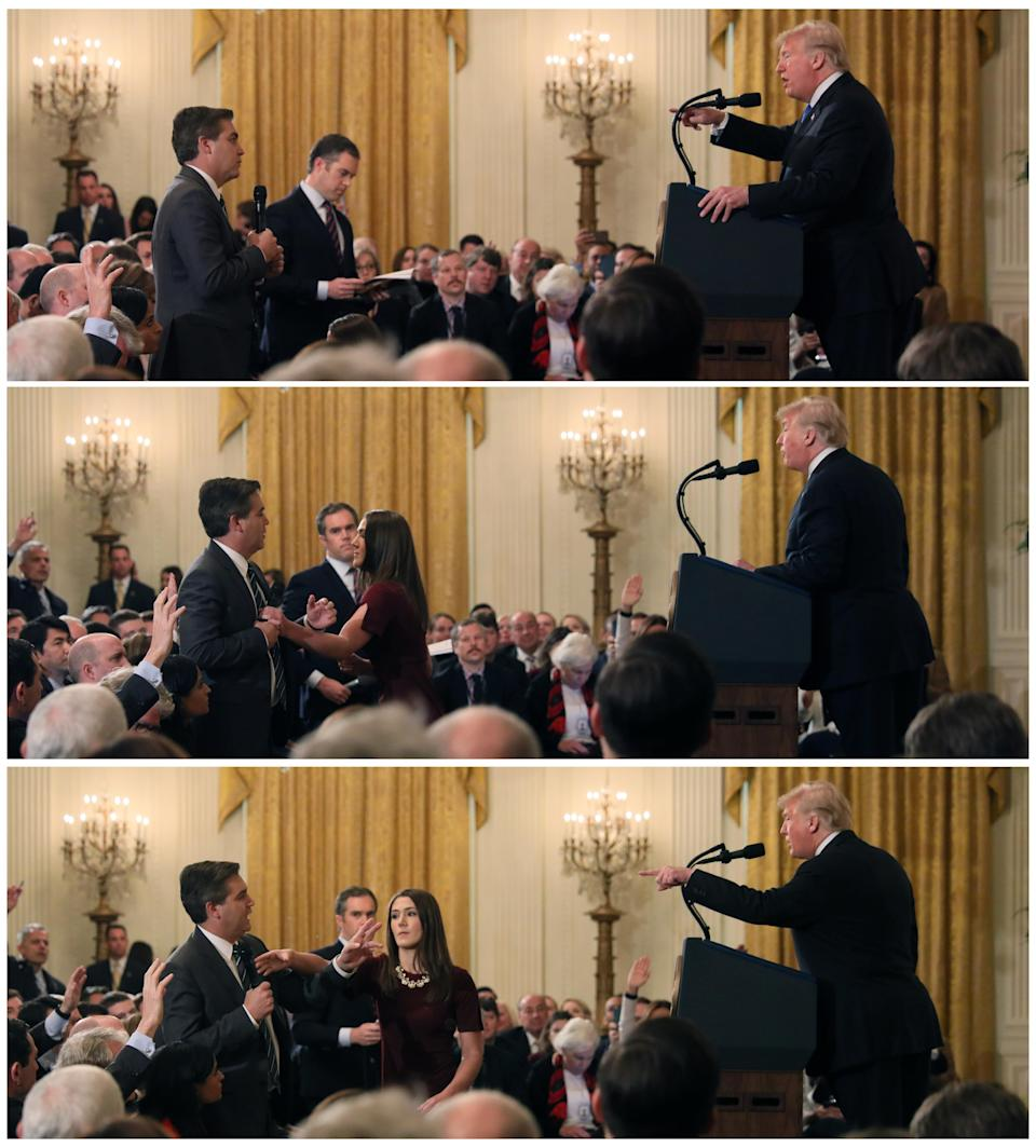 <em>The White House staff member reaches for the microphone held by CNN's Jim Acosta as he questions Trump (Reuters)</em>