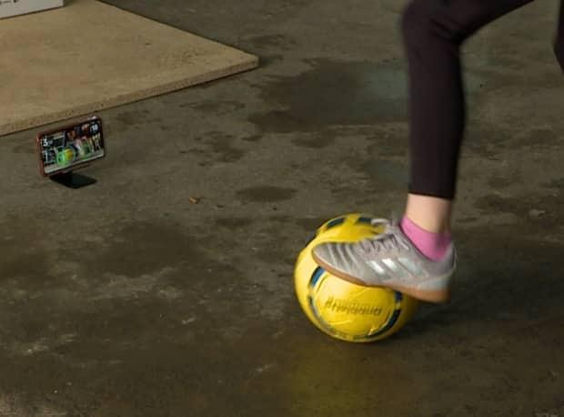 A young Feildians player tests out a smart soccer ball.