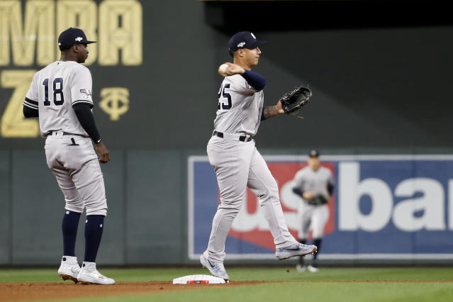 New York Yankees second baseman Gleyber Torres, right, throws to first base in front of teammate Didi Gregorius, left, during a double play in the first inning in Game 3 of a baseball American League Division Series, Monday, Oct. 7, 2019, in Minneapolis. (AP Photo/Bruce Kluckhohn)