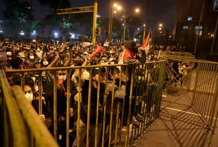 Demonstrators gather behind fences during protests that led to the resignation of Peru's interim President Manuel Merino, in Lima