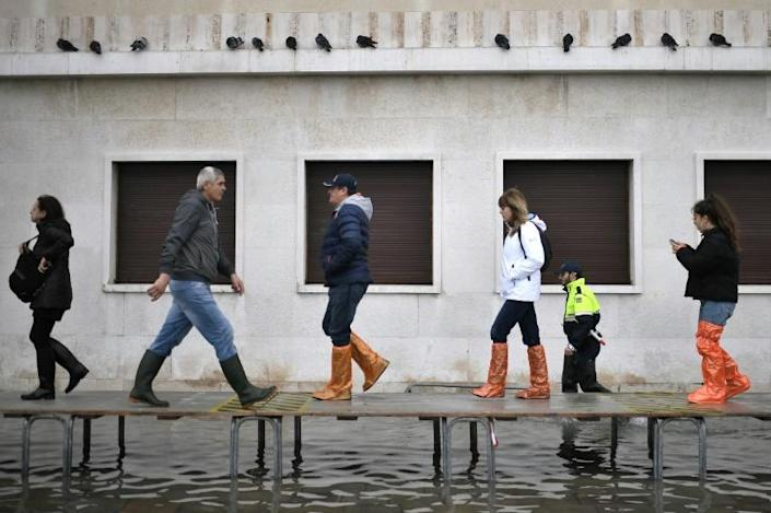 Officials erected a footbridge across a flooded street after the tide hit (AFP Photo/Marco Bertorello)