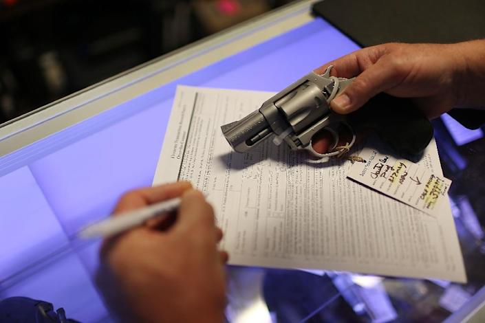 A man fills out his Federal background check paperwork as he purchases a handgun at the K&W Gunworks store on January 5, 2016 in Delray Beach, Florida (AFP Photo/Joe Raedle)