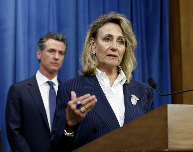 """FILE - In this July 23, 2019, file photo, Marybel Batjer, of the California Public Utilities Commission, speaks during a news conference as Gov. Gavin Newsom looks on in Sacramento, Calif. California's utility regulator is issuing a series of sanctions against Pacific Gas and Electric for what it calls """"failures in execution"""" during the largest planned power shut-off in state history to avoid wildfires. Batjer said Monday, Oct. 14, 2019, the utility needs to have a goal of restoring power within 12 hours instead of its current 48 hours, minimize the scale of future outages and better communicate with the public and local officials. (AP Photo/Rich Pedroncelli, File)"""