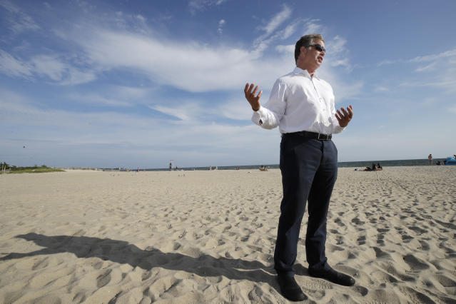 In this Aug. 21, 2019 photo, Andrew Gottlieb, executive director of the Association to Preserve Cape Cod, stands on Covell Beach in Centerville, Mass. near where the Vineyard Winds' proposed buried energy cables would stretch from offshore wind turbines, through the ocean, under the sand and parking lot, to a landing point onshore. The cables would then extend to a grid connection point inland. But as Trump has made clear how much he hates wind turbines, all the offshore wind projects, including the nation's first utility-scale offshore wind project, an 84 turbine, $2.8 billion wind farm slated to rise 15 miles off Martha's Vineyard, have stalled. (AP Photo/Elise Amendola)