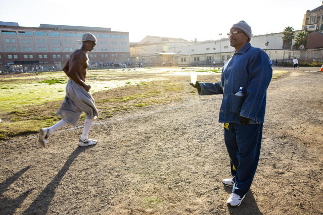 FILE - In this Friday, Nov. 22, 2019 file photo, Clifton Williams, right, hands out water as Wallace Jackson completes another lap around the prison yard in the San Quentin State Prison marathon in San Quentin, Calif. Aged 22 to 72, the competitors are all members of the maximum-security prison's 1,000 Mile Club and include inmates incarcerated for rape, attempted murder and other charges. (Santiago Mejia/ San Francisco Chronicle via AP)